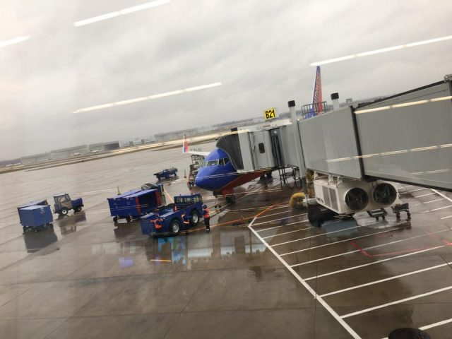 An airplane and luggage sitting at the gate